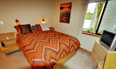 Photo of the bedroom showing the tv & view from one of the windows of the river.