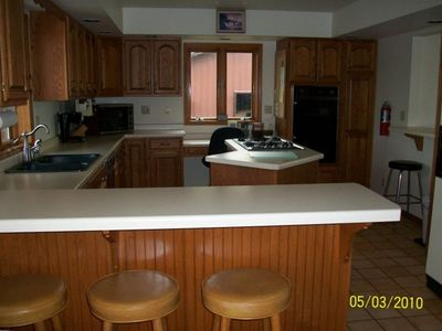 Huge kitchen with breakfast bar, stocked with all dishes & cookware.