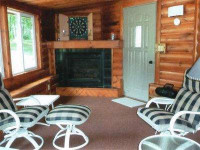 Three-season porch features comfortable seating near gas fireplace.