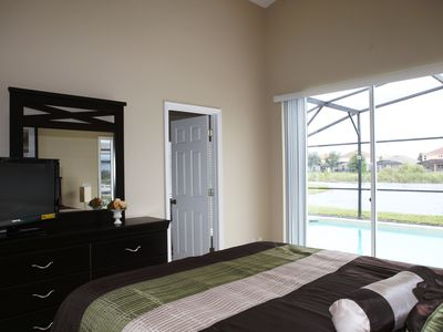 "Master bedroom with queen bed, ceiling fan, 32"" TV, open to pool deck and lake"