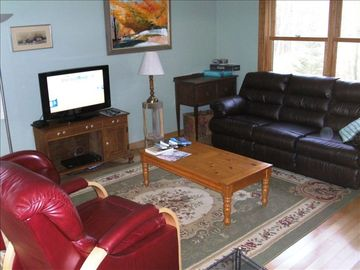 Living room has big screen TV with cable, two leather chairs and a recliner sofa