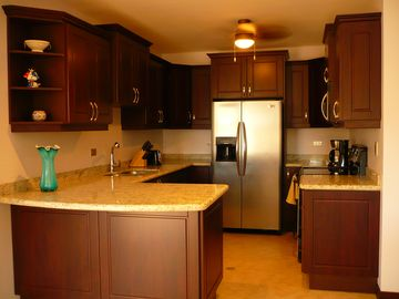 The kitchen features brand-new stainless steel appliances + granite counter tops
