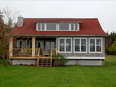 Cottage with new outdoor deck and enclosed sunroom.