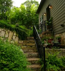 The dozen old stone steps leading up to the apartment door. New safety railing. - Austin studio vacation rental photo
