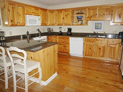Cook in this well stocked kitchen with granite countertops and barstools.