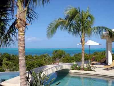 The pool winds amid palm trees and lush, tropical landscaping...
