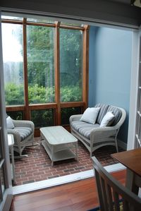 Sun room off of dining room with wicker loveseat and rocker.