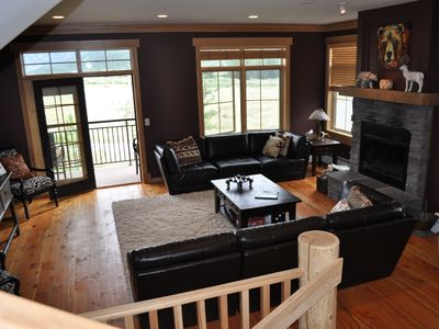 Living room w/fire place and deck looking out on golf course