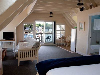 The king size bed in the oversized living area looking out toward the deck.