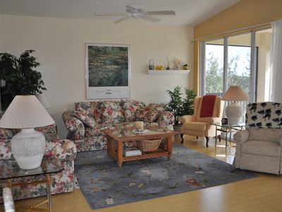 Living room facing lanai overlooking ninth green of Pelican Sound golf course.
