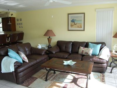 Living room with new brown leather couches, queen sleeper sofa and crown molding