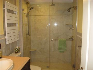 Large tiled shower with 3 heads (1 adjustable). Also shown is heated towel rack