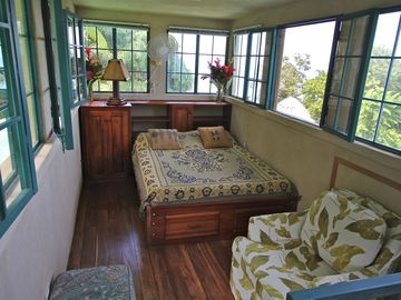 Double bed in the Crows nest bedroom with 360 degrees windows