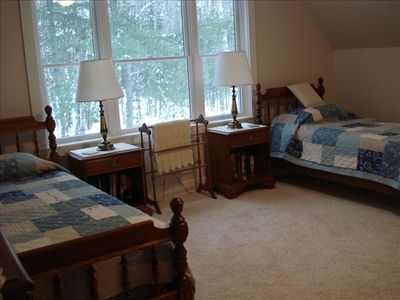Large 3rd bedroom has comfortable  twin beds and walk-in closet. View of woods.