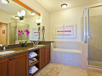 Spacious master bath has soaking tub and large glass-enclosed shower with bench