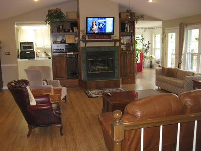Open Living room with TV, gas fire place, leading to kitchen and dining room.