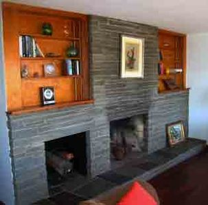 Main livingroom has a field-stone fireplace with plenty of reading material...