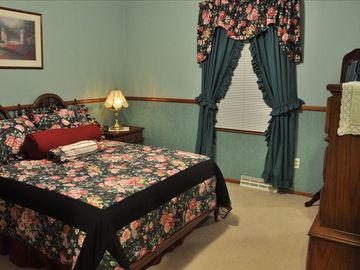 The Green Room, complete with double bed, dresser, and standing mirror