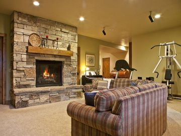 Family rec room with gas fireplace, fitness equipment, and big screen tv