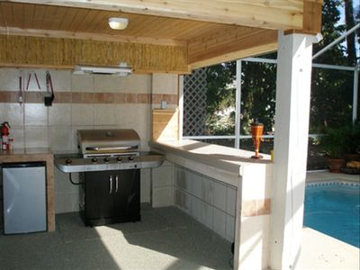New kitchenette in pool area w/ mini refrigerator, gas grill, & bar seating