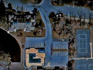 Property satellite view: condo (with hand icon), parking, pool and tennis crts.