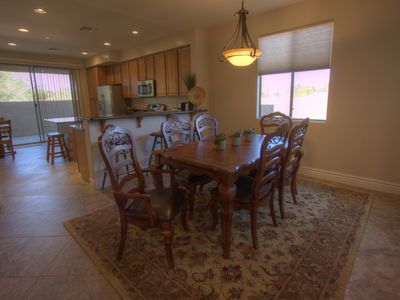 Dining area, breakfast bar, kitchen island and cafe table near sliding door.