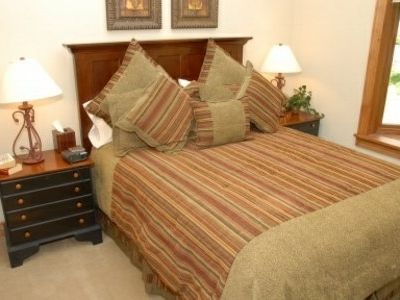 The second guest room offers a queen sized bed, luxury linens, and a large bay window.