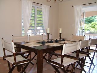 Rincon house photo - Dining room w/ French doors to Front Porch: table seats 8 + 4 counter stools.