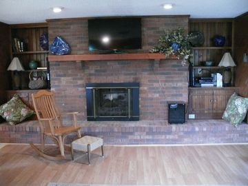 View of gas fireplace and 42 inch TV in large living area.