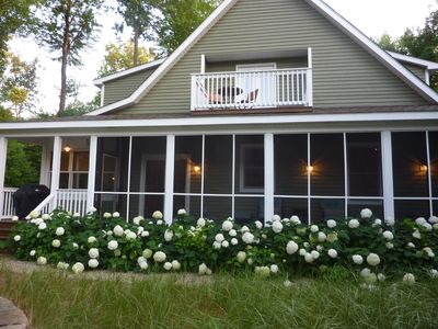 Side of the house with a screened in porch and master bedroom balcony.