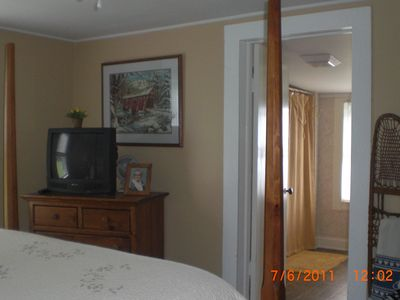 This bedroom also has a TV and convenient access to the bath.