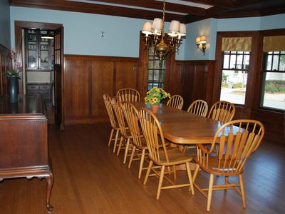 The wood paneled dining room has a large table and room for additional tables.
