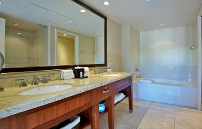 Master bathroom with dual sinks bathtub, enclosed glass shower and toilet closet