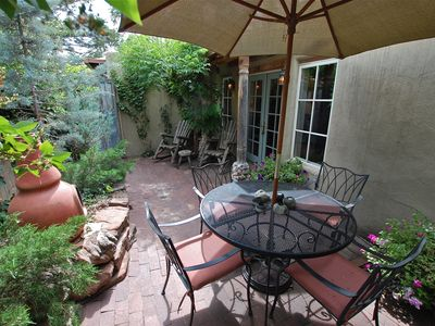 A Pretty, Shaded Dining Spot in the Courtyard Features a Chiminea Fireplace