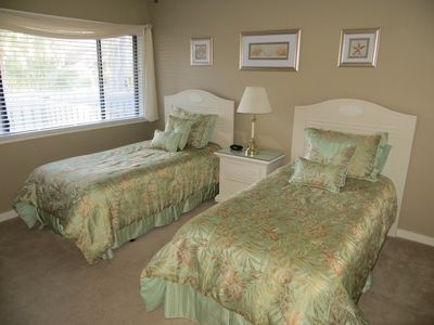 Extra bedroom with twin beds, dresser with mirror and large closet