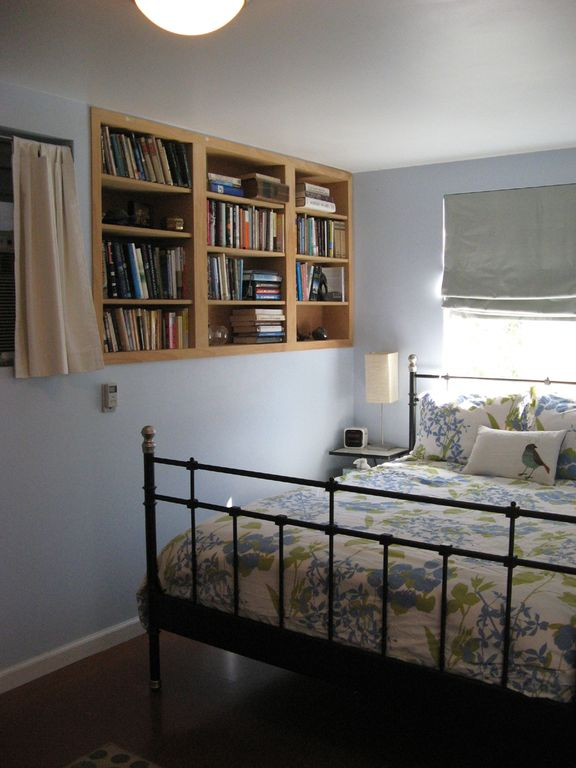 queen-sized bed with diverse bedside reading options