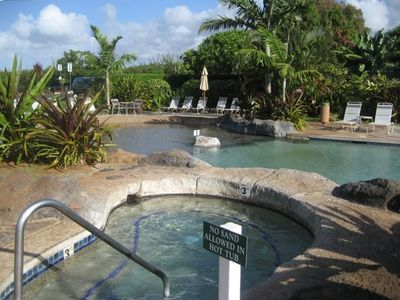 The swimming pool has a slide and shallow, sandy area, as well as a hot tub.