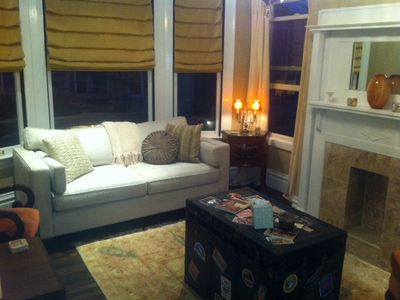 Beautifully furnished living room with wool rug & historic steamer trunk.