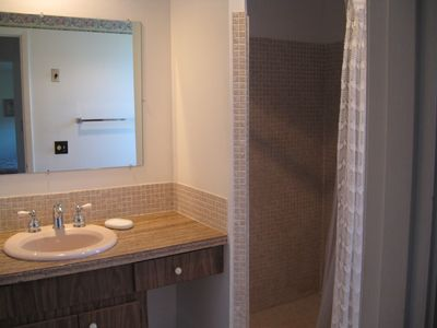 Masterbath has tile shower, tile floor and large wall mirror.