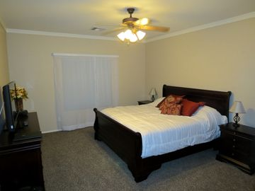 "Master bedroom with king size bed and 40"" flat screen TV"