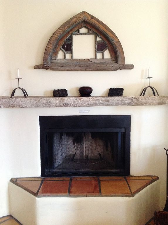 Antique wood mantel and saltillo tile accent the wood-burning fireplace