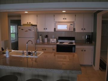 Spacious kitchen with lots of counter and floor space. Pantry behind.