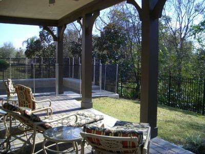 Pool and Patio Overlook Conservation Area With Comfortable Outdoor Furniture