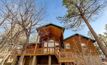 Show Low cabin rental - 35ft Tall Picture Window views overlook 80 acre Prairie and mountains.