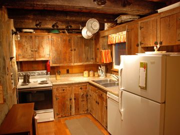 Rustic decor in kitchen. Amenities include electric stove, microwave, dishwasher