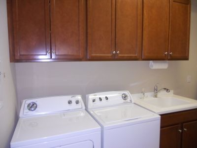 Convenient laundry room with storage and sink leads to 2 car attached garage
