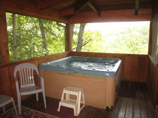 Gatlinburg cabin photo - Hot tub on the screened deck with sitting area nearby.