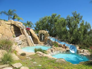 Malibu house photo - Lovely pool and waterslide make a beautiful backdrop for any event.