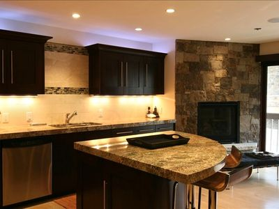 kitchen,island, fireplace, and sliding glass doors out to balcony