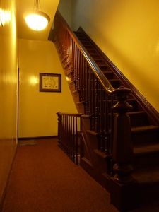 The Original 1907 Staircase of Carved Wood Leads Up Through The Townhouse Today